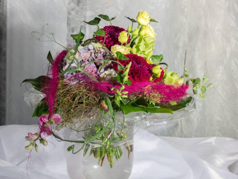 Ein Blumenstrauß mit Hortensienblüte, Rosen, Dahlien, Wicke, Efeu und Zierelementen in einer Glasvase