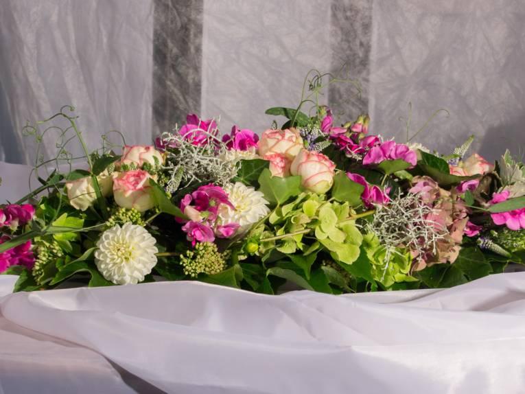 Ein Tischgesteck mit Dahlien, Rosen, Wicken, Hortensienblüte, Efeu auf weißem fließenden Tuch