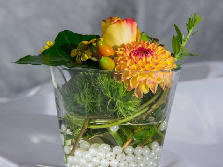 In einem Wasserglas liegen auf Glasperlen und Wasser Blumenblüten