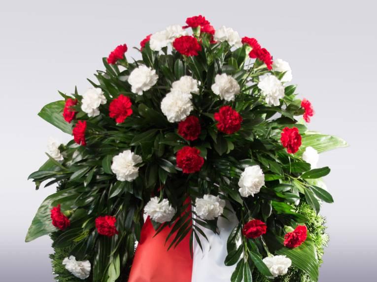Rote und weiße Nelken mit Blattgrün passend zur rot-weißen Schleife des Kondolenzgestecks