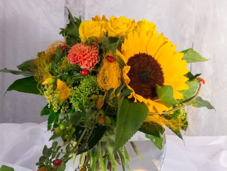 Ein Blumenstrauß in Gelbtönen mit roten Akzenten: Sonnenblume, Dahlie, Rosen, Hagebutten und Sedum mit Blattgrün werden von roten Marienkäfern geziert.