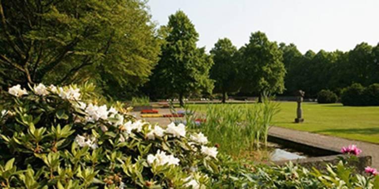 Über Rhododendren und ein Wasserbecken blickt man auf eine Statue, die auf einem gepflegten Rasen im Stadtpark steht.