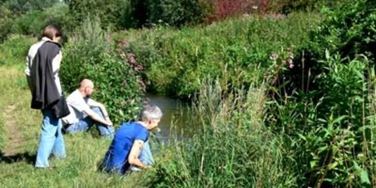 Drei Menschen an einem Bachlauf im Sommer