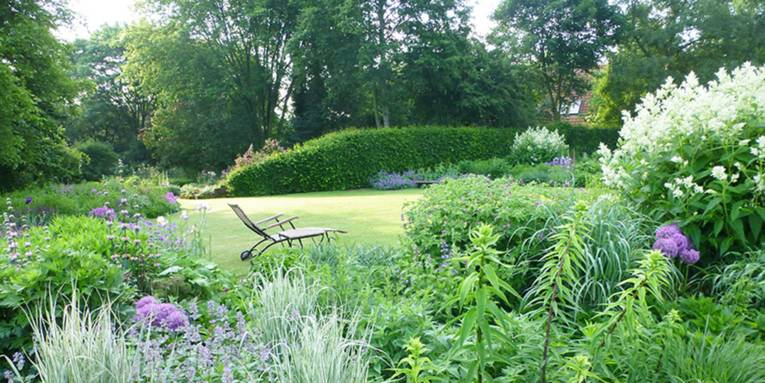 Blick in einen Garten, dessen Stauden in weiß und violett leuchten. Auf dem gepflegten Rasen vor einer Buchenhecke lädt ein Liegestuhl zum Verweilen ein.