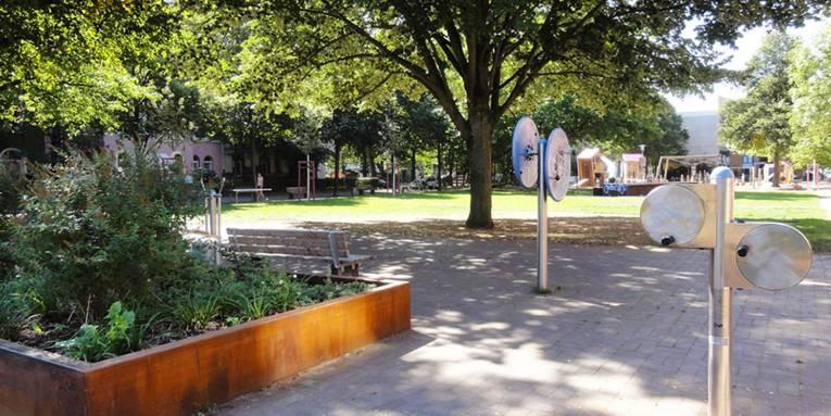 Blick auf Fitnessgeräte für die Arme, die im Schatten eines großen Baumes auf einem Platz stehen