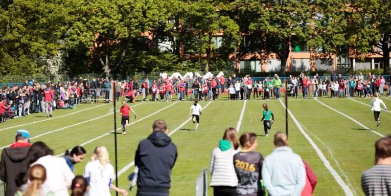Laufende Kinder auf einem Sportplatz.