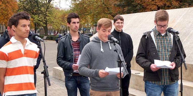Einige Schüler, die Texte am Holocaust-Mahnmal vortragen