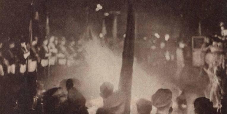 """Bücherverbrennung im Mai 1933 in Hannover. Erkennbar haben Vertreter verschiedener studentischer Verbindungen mit ihren Fahnen (links oben) Aufstellung um den brennenden Scheiterhaufen für die Bücher genommen. Abgedruckt in """"Die Weltschau"""" vom 21.05.1933, S. 2."""
