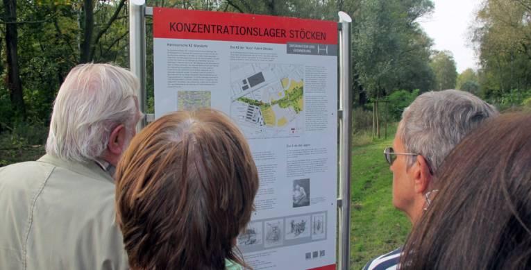 Teilnehmer einer Fahrradtour betrachten die Informationstafel zum KZ Stöcken, 2014