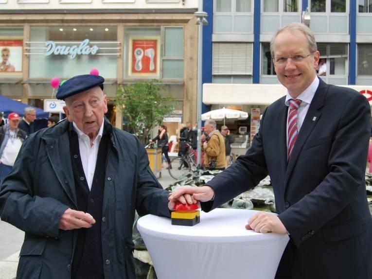 Emil Cimiotti und Stefan Schostok drücken gemeinsam einen roten Knopf, um den Blätterbrunnen wieder in Betrieb zu nehmen