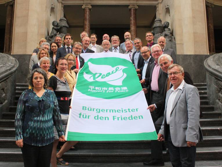"Knapp 30 Personen zeigen die Flagge der ""Mayors for Peace"""