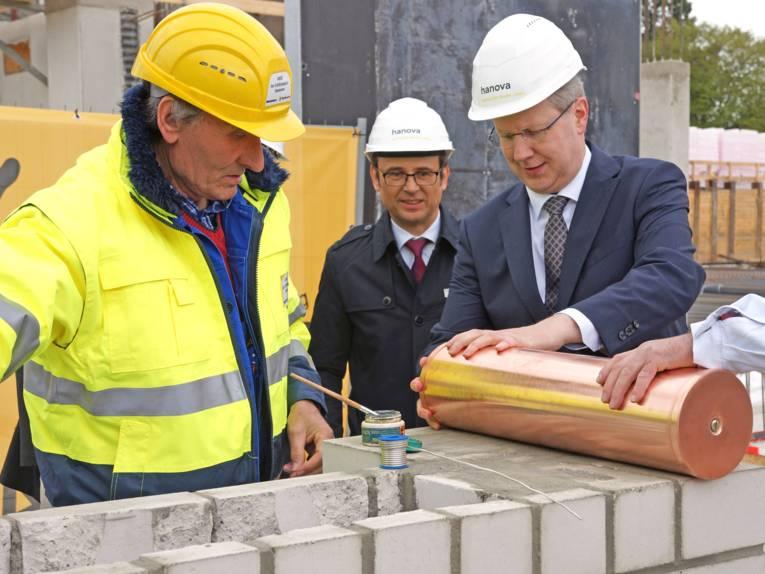 Drei Männer auf einer Baustelle.