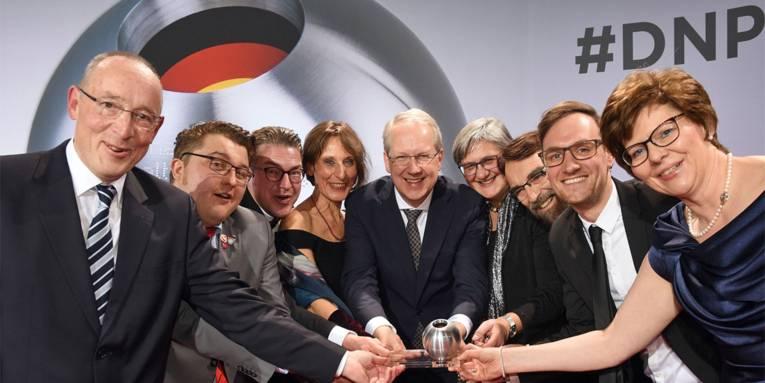 Gruppenbild der Hannoverschen Delegation in festlicher Garderobe mit dem gewonnenen Deutschen Nachhaltigkeitspreis in der Mitte
