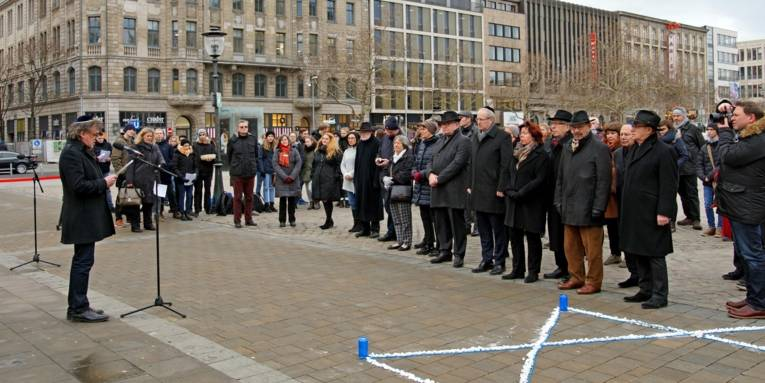 Menschen in Gedenken auf einem Platz.