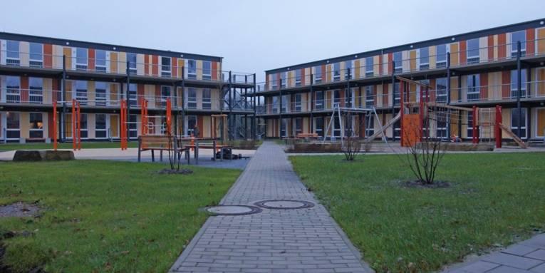 Gebäude von außen, davor ein kleiner Spielplatz.
