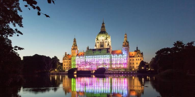 Bunt beleuchtetes Rathaus. Davor ein Teich.