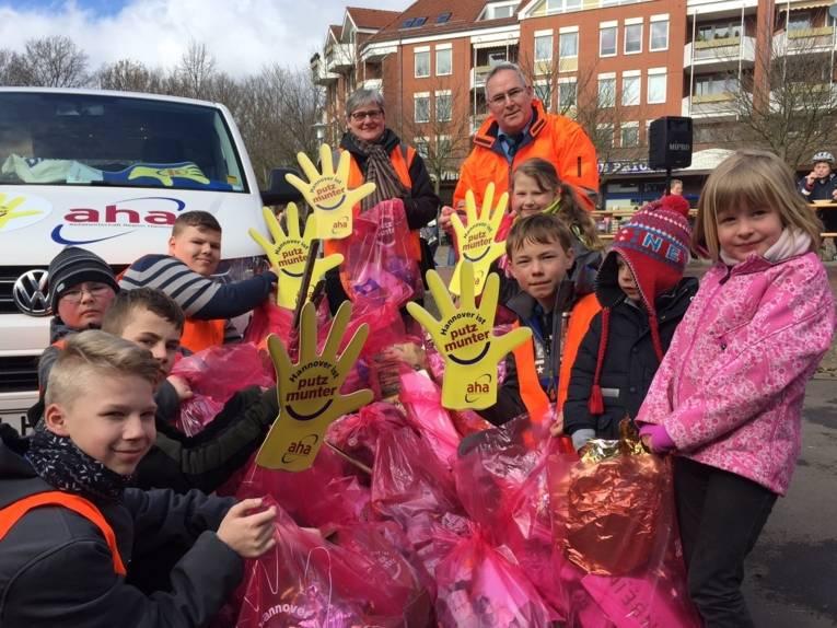Erwachsene und Kinder mit Mülltüten.