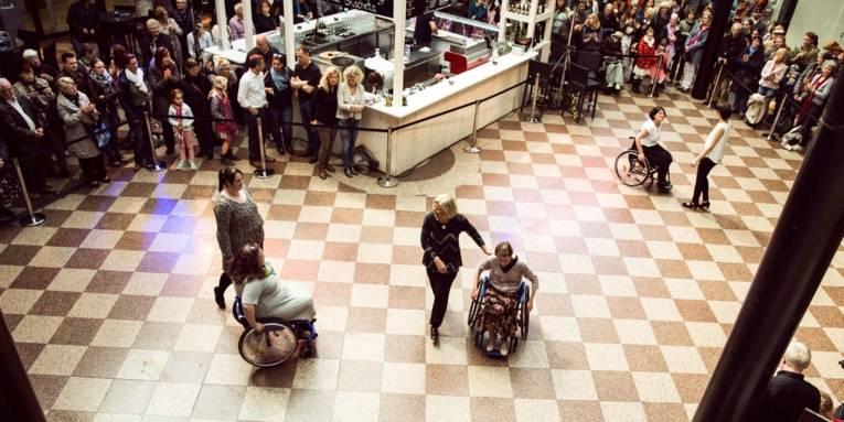 Rollstuhlfahrende auf einer großen Fläche in einer Galerie.