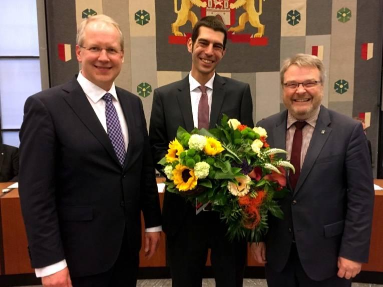 Drei lächelnde Männer in einem Saal.