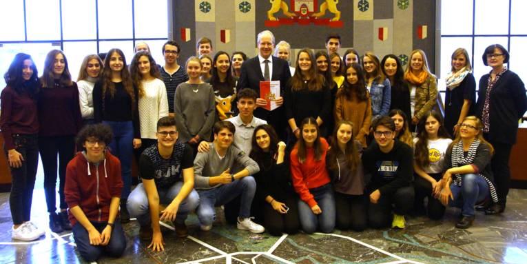 Schülerinnen und Schüler mit Erwachsenen in einem Saal.