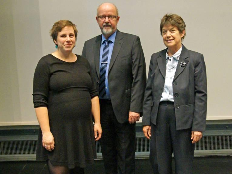 Zwei Frauen und ein Mann vor einer weißen Wand.