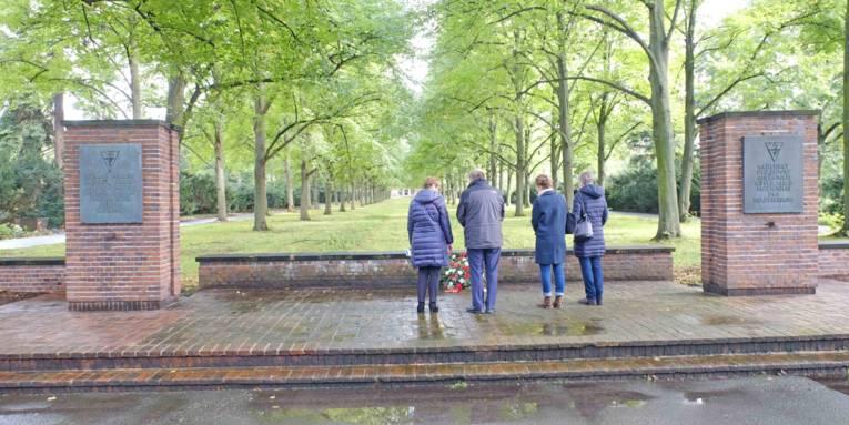 Ein Mann und drei Frauen vor einem Mahnmal.