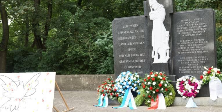 Blumenkränze vor dem Denkmal am Ehrenfriedhof.
