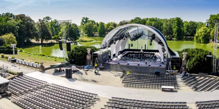 Eine Bühne vor einem Teich. Davor leere Stuhlreihen.