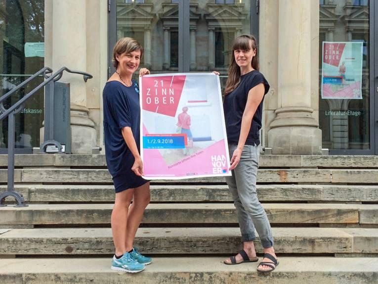 Zwei Frauen stehen auf einer Treppe und präsentieren das Plakat einer Kulturveranstaltung