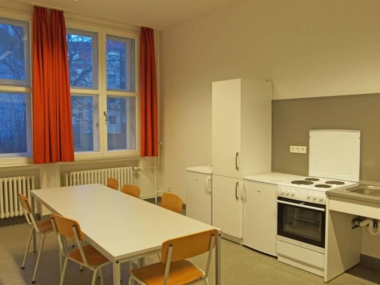 Küche mit Tischen und Stühlen.