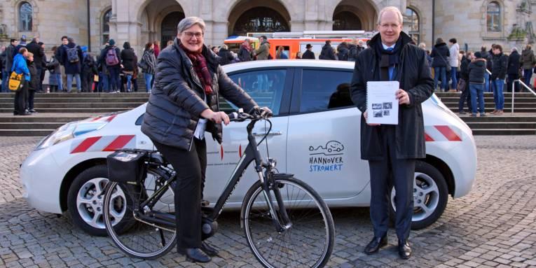 Eine Frau auf einem Fahrrad und ein Mann mit einer Mappe vor einem Auto.