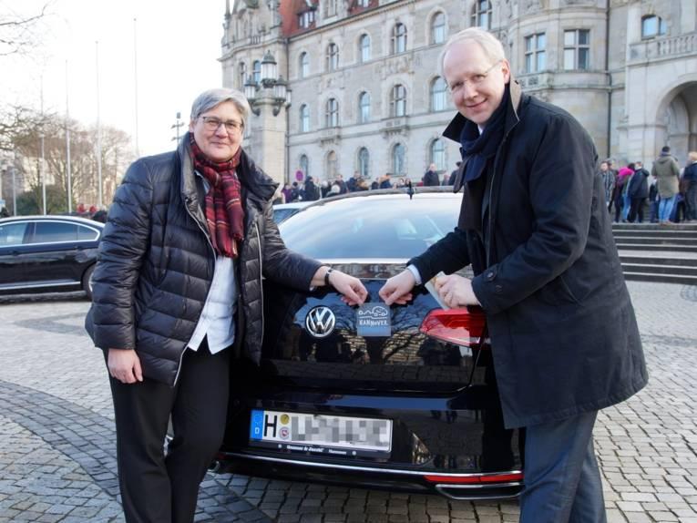 Eine Frau und ein Mann, die eine Plakette an einem Auto anbringen.