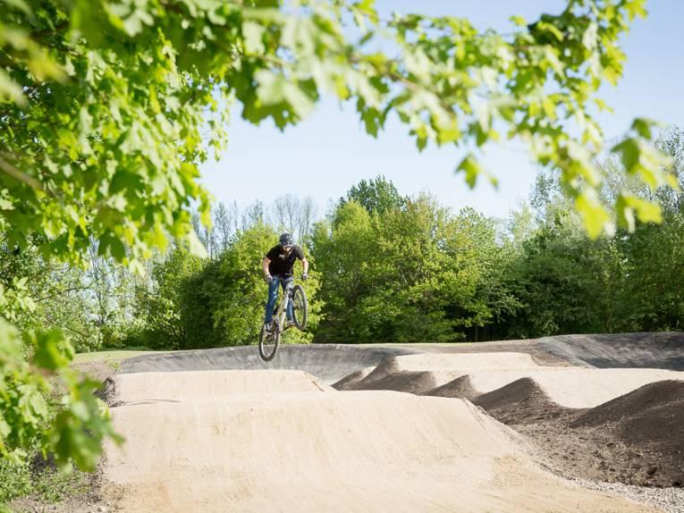 Ein BMX-Fahrer springt über einen Hügel auf einer BMX-Bahn