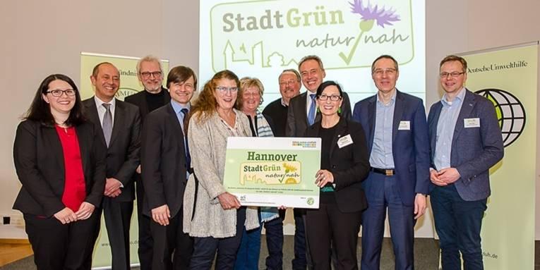 """Gruppenfoto: Im Vordergrund halten Bürgermeisterin Regine Kramarek und Projektleiterin Annemarie Hische gemeinsam ein Schild mit dem Label """"Hannover Stadtgrün naturnah"""", dahinter stehen weitere Personen, die sich freuen."""