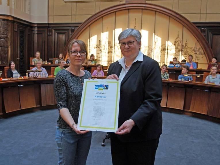 Zwei Frauen mit einer Urkunde.