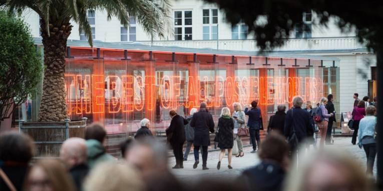 Menschen vor einem beleuchteten Gebäude.