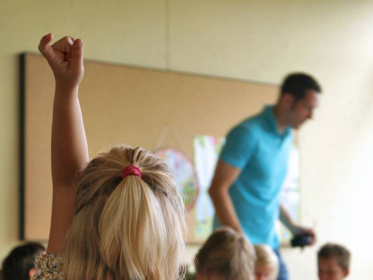 In einem Klassenraum ist ein Kind von hinten zu sehen, wie es sich meldet.