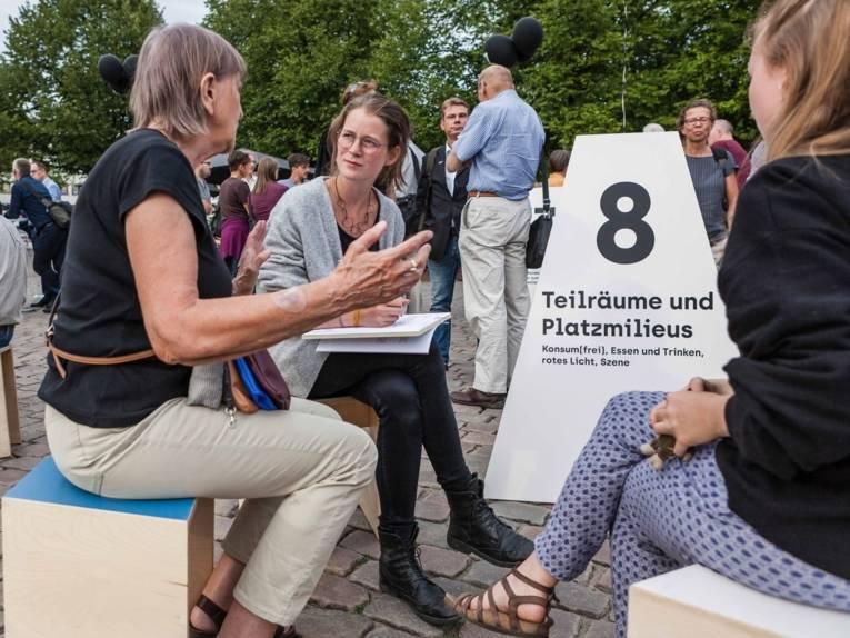 Menschen im Gespräch auf einem Platz.
