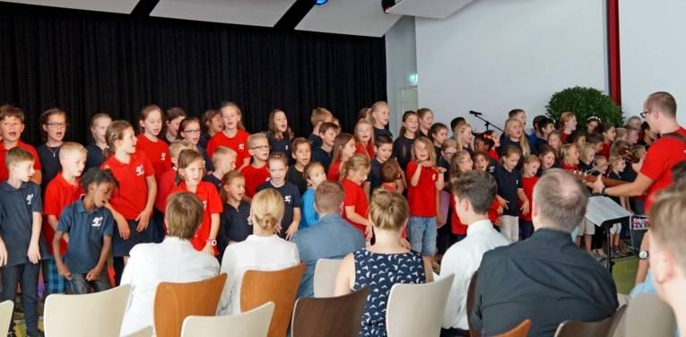 Schulchor in einer Halle. Davor Publikum.