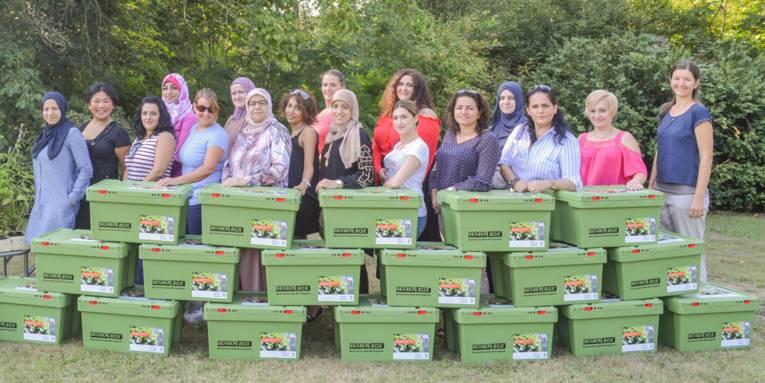 Eine Gruppe Frauen steht hinter Unterrichtskisten