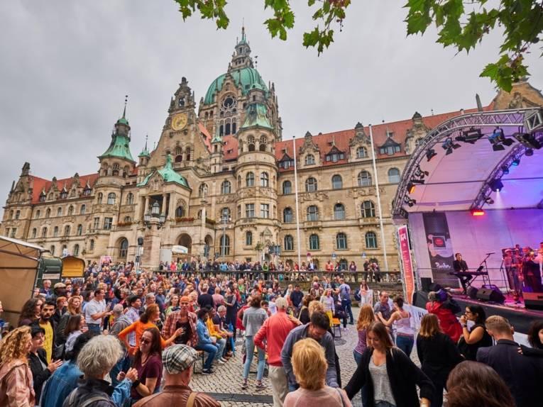 Menschen auf einem Platz, im Hintergrund ein Rathaus. Rechts im Bild steht eine Bühne.