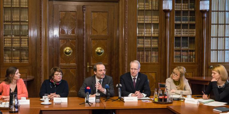 Sechs Personen auf einer Pressekonferenz