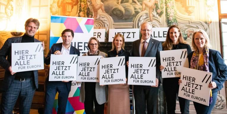 """Sieben Personen präsentieren die Leitidee """"HIER JETZT ALLE für Europa"""" zu Hannovers Bewerbung als Kulturhauptstadt Europas 2025"""