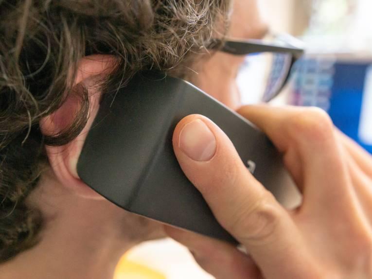 Ein Mann hält sich einen Telefonhörer ans Ohr