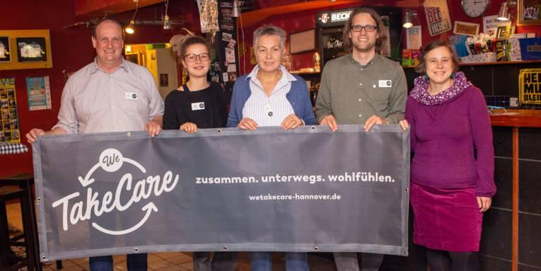 """Fünf Personen stehen vor einer Theke und halten ein Banner zur Kampagne """"We Take Care"""" hoch."""
