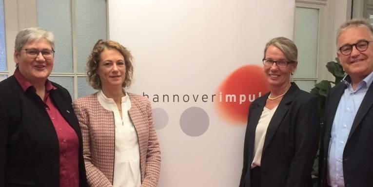 Die erste Stadträtin Sabine Tegtmeyer-Dette, Marina Barth als Vertreterin der Wirtschaft im Aufsichtsrat, Doris Petersen und Regionspräsident Hauke Jagau stehen vor einem Banner mit dem Logo von hannoverimpuls.