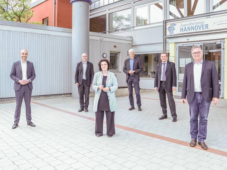 Sechs Personen vor einem Gebäude – dazwischen viel Abstand.