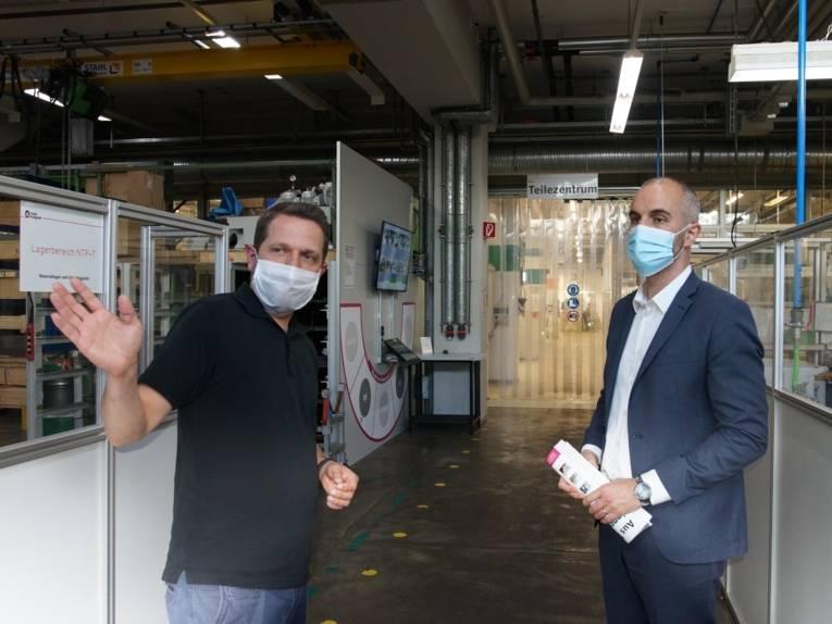 Zwei Männer in einer Fertigungshalle.