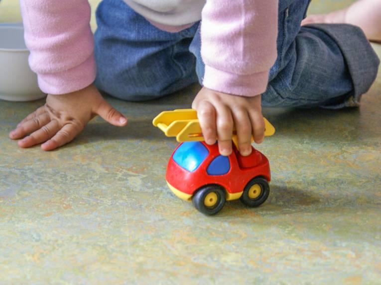 Ein Kind, das mit einem Spielzeugauto spielt