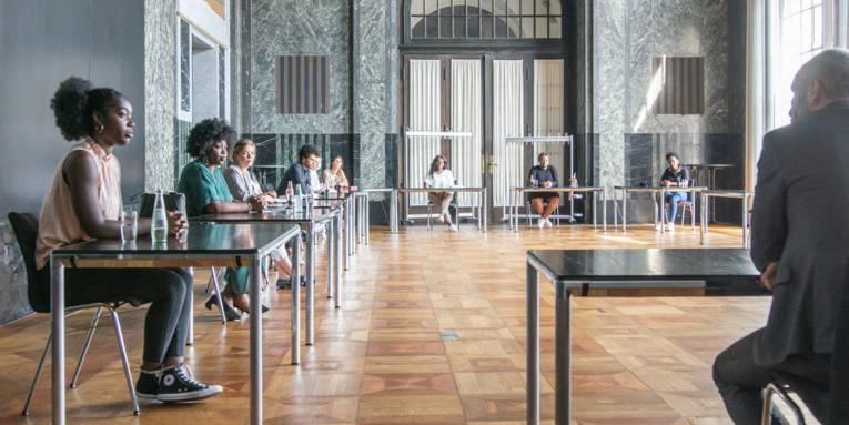 Ein großer Saal, in dem an jeweils einzelnen Tischen zehn Menschen sitzen und im Gespräch miteinander sind